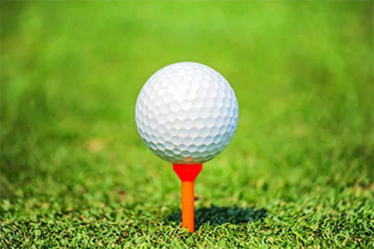 close up golf ball with tee on green grass