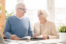 Happy senior couple in smart casualwear looking at each other while sitting by desk and looking through magazine