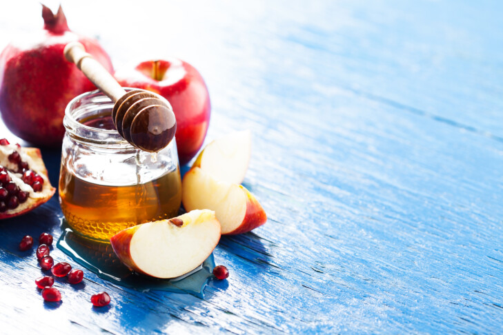 Rosh hashanah (jewish holiday) concept: honey, apple and pomegranate, with space for text